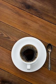 Xícara de café isolada na mesa de madeira. vista superior, plana leigos bebida de café com espaço de cópia. imagem vertical.