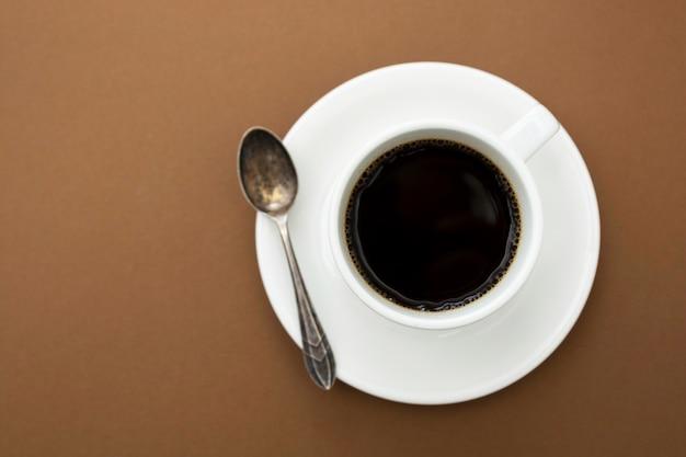 Xícara de café isolada na mesa marrom. bebida de café com espaço de cópia.