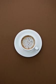 Xícara de café isolada na mesa marrom. vista superior, plana colocar bebida de café preto com espaço de cópia.
