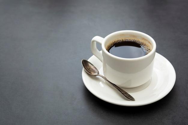 Xícara de café isolada. xícara de café branca vista superior colher e prato em fundo escuro