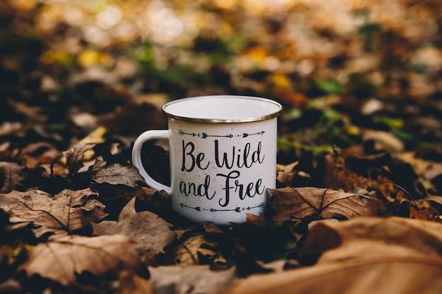 Xícara de café isolado no meio do chão em uma floresta de outono com fundo de folhas caídas