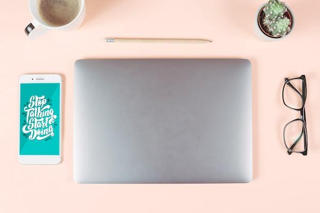Xícara de café; lápis; óculos; pote de cacto; telefone inteligente e laptop em fundo colorido