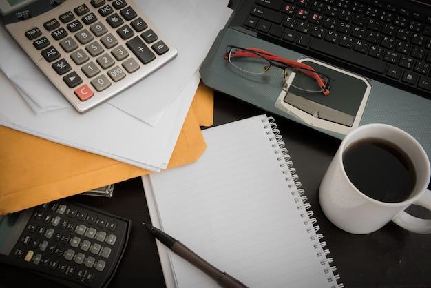 Xícara de café, laptop, arquivo de documentos, caneta, calculadora, bloco de notas e óculos na mesa de madeira