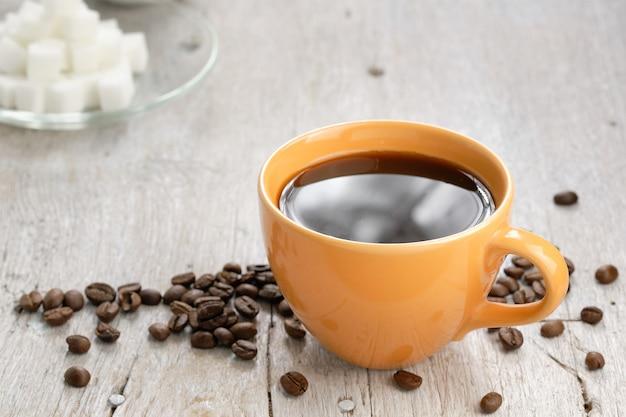 Xícara de café laranja, açúcar cúbico e grãos de café, algumas peças foram derramadas na mesa de madeira.