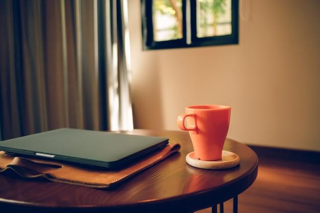 Xícara de café laranja e laptop em cima da mesa no café.