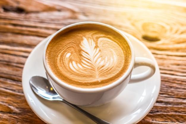 Xícara de café latte art com colher e prato na casca marrom