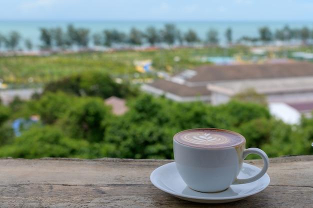 Xícara de café latte art em mesa de madeira com vista para o mar na praia de samila, província de songkhla, tailândia