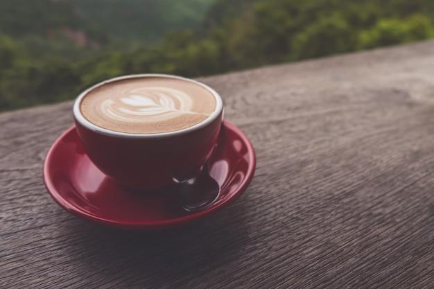 Xícara de café latte art na mesa de madeira, plana leigos