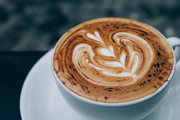 Xícara de café latte art quente na mesa de madeira