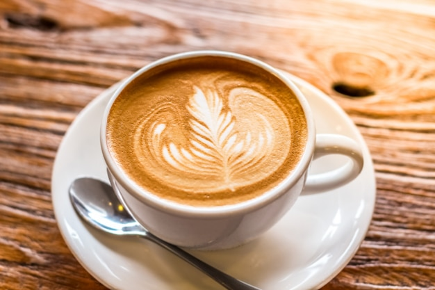 Xícara de café latte art sobre a textura bonita de casca marrom com luz quente