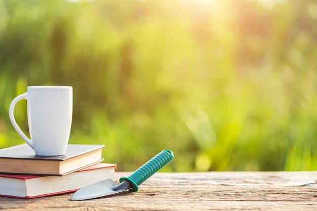 Xícara de café, livro e equipamento de jardim na mesa de madeira com luz solar no tempo da manhã