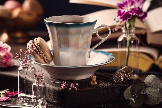 Xícara de café, livros antigos e flores cravos rosa na superfície de madeira velha. dia das mães, cartão de aniversário. copie o espaço