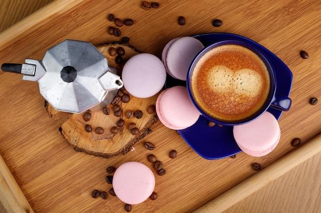 Xícara de café macaroons e grãos de café em uma bandeja e cafeteira gêiser em uma bandeja de madeira vista superior