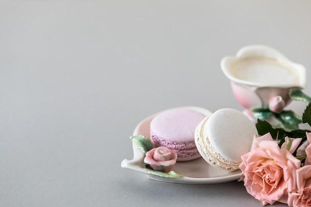 Xícara de café, macarrão para bolo e rosas cor de rosa em um fundo cinza. copie o espaço.