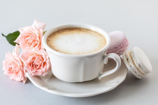 Xícara de café, macarrão para bolo e rosas cor de rosa em uma superfície cinza. copie o espaço.