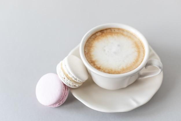 Xícara de café, macarrão para bolo em um fundo cinza e rosa. copie o espaço.