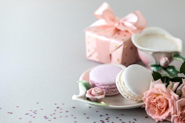 Xícara de café, macarrão para bolo, um presente em uma caixa e rosas cor de rosa em um fundo cinza. copie o espaço.