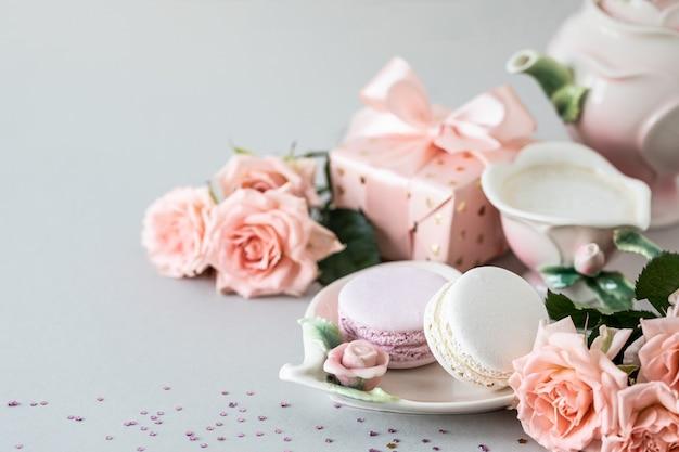 Xícara de café, macarrão para bolo, um presente em uma caixa e rosas cor de rosa em uma superfície cinza