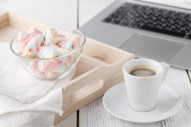 Xícara de café, marshmallow torcido e notebook