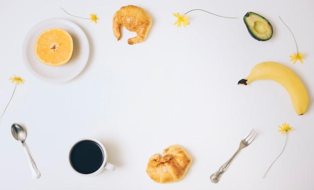 Xícara de café; meia laranja; croissants; abacate; banana; croissants e xícara de café com espaço de cópia de texto