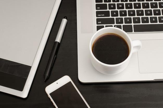Xícara de café, mesa digitalizadora com uma caneta, parte do laptop e telefone na mesa de madeira preta, close-up