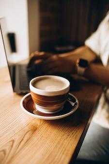 Xícara de café na mesa ao lado do laptop