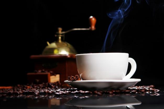 Xícara de café na mesa com grãos de café ao redor
