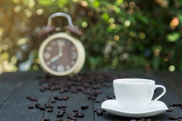 Xícara de café na mesa da manhã com grão de café e despertador fundo