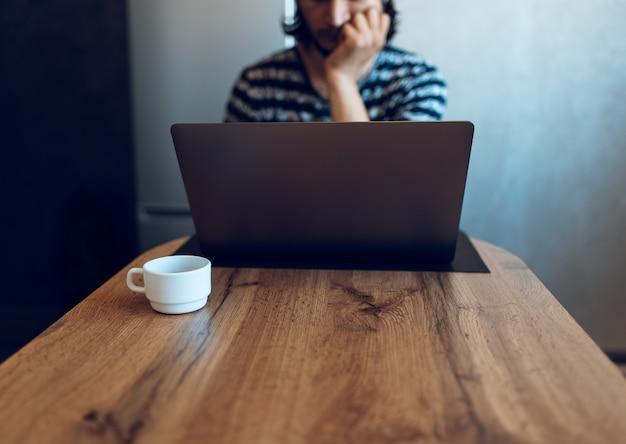 Xícara de café na mesa de madeira contra o fundo do homem que trabalha no laptop.