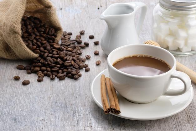Xícara de café na mesa de madeira de manhã com feijão de café, açúcar cubo e canela. - imagem