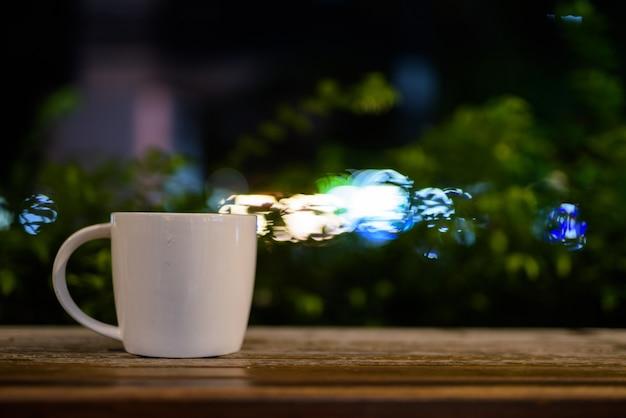 Xícara de café na mesa de madeira do restaurante à noite