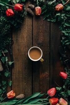 Xícara de café na mesa de madeira escura com tulipas e várias folhas. postura plana.