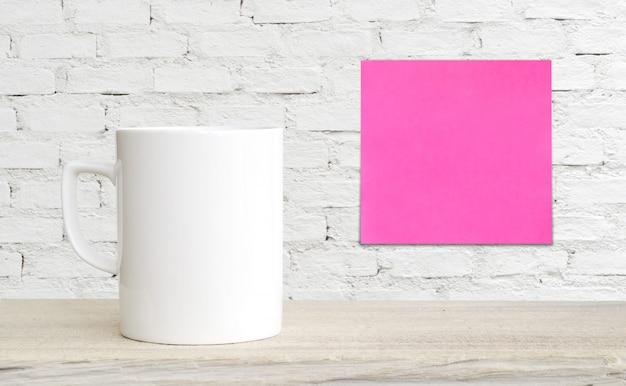 Xícara de café na mesa e papel em branco do bloco de notas na parede de tijolo branco