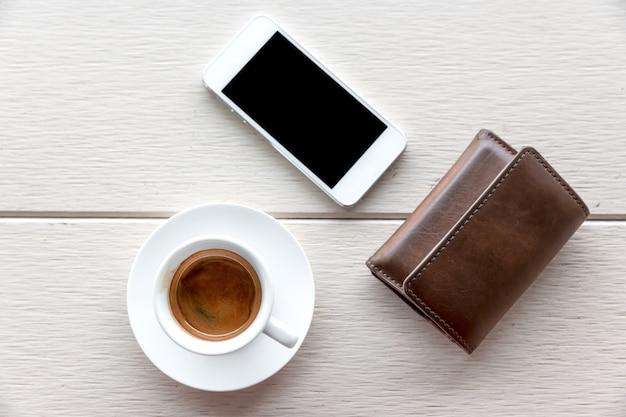 Xícara de café na mesa e telefone celular, carteira
