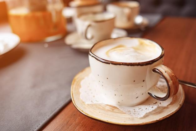Xícara de café na mesa, latte art, luz do sol