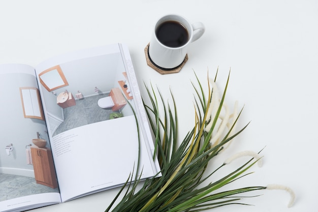 Xícara de café na mesa perto de um jornal e plantas