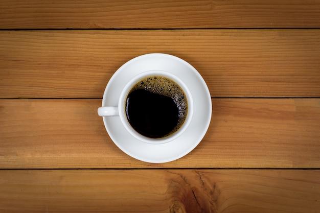 Xícara de café na opinião superior do fundo de madeira.
