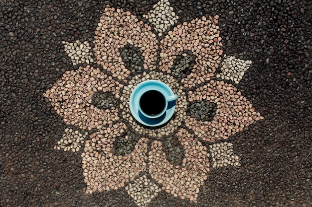 Xícara de café na pavimentação de flores de estilo balinês.