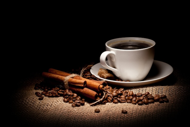 Xícara de café na sacaria e canela