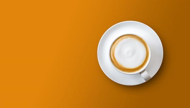 Xícara de café na superfície laranja