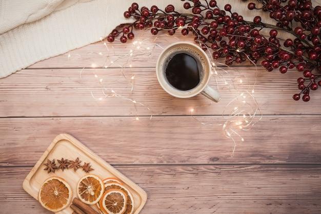 Xícara de café na tabela de madeira, na laranja secada e na canela, nas bagas e nas luzes, vista superior.