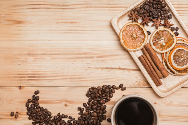 Xícara de café na tabela de madeira, na laranja secada e na canela, vista superior.