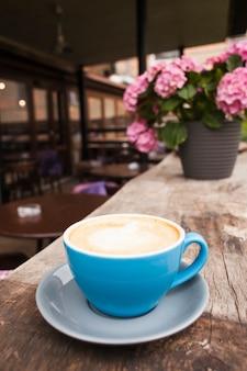 Xícara de café na velha mesa de madeira texturizada no café vazio
