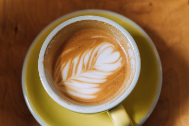 Xícara de café na vista superior de mesa de madeira. leite alternativo. fundo de madeira de meados do século. arte em espuma