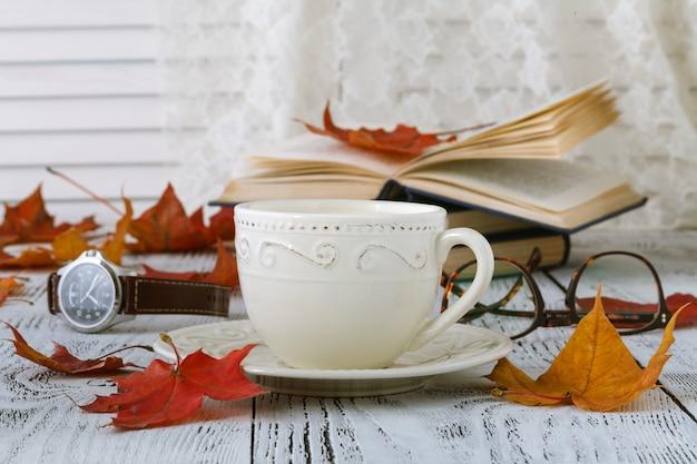 Xícara de café nas folhas de outono outono e superfície de superfície de madeira
