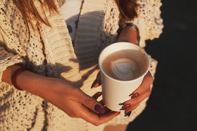 Xícara de café nas mãos. mãos de mulher segurando um copo de papel de um café.