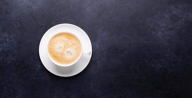 Xícara de café no banner horizontal de pedra preta
