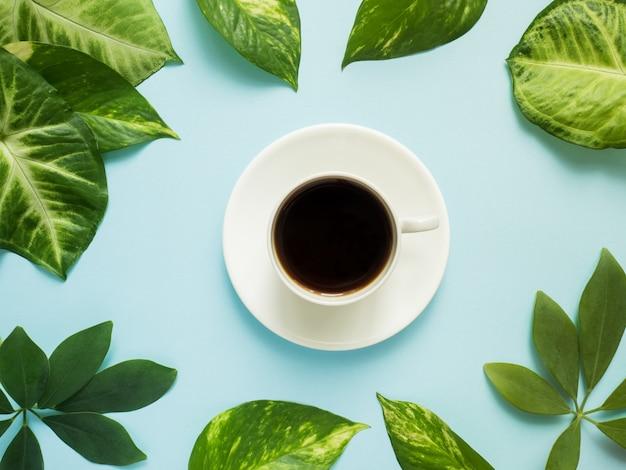 Xícara de café no centro no fundo azul com folhas verdes.