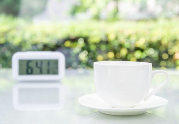Xícara de café no escritório com relógio digital