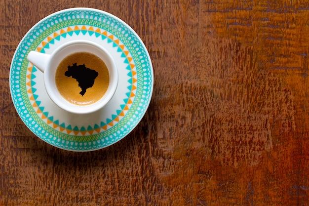 Xícara de café no formato brasil em mesa de madeira